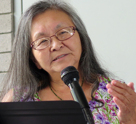 Lola Jong, speaking into a microphone at a podium