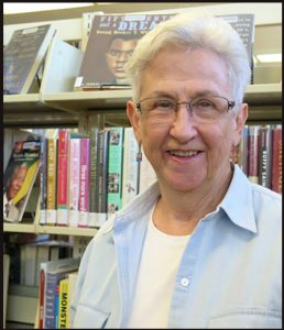 photo of Lee Crosby in front of library book shelves