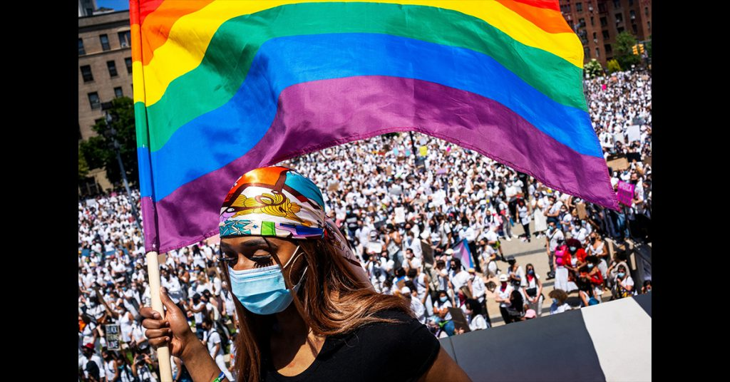 photo from the New York Times showing African American woman wearing mask raising the rainbow flag in a square in Washington DC
