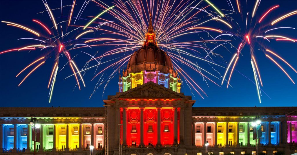 image showing San Francisco City Hall, lit in rainbow colors with fireworks in sky above